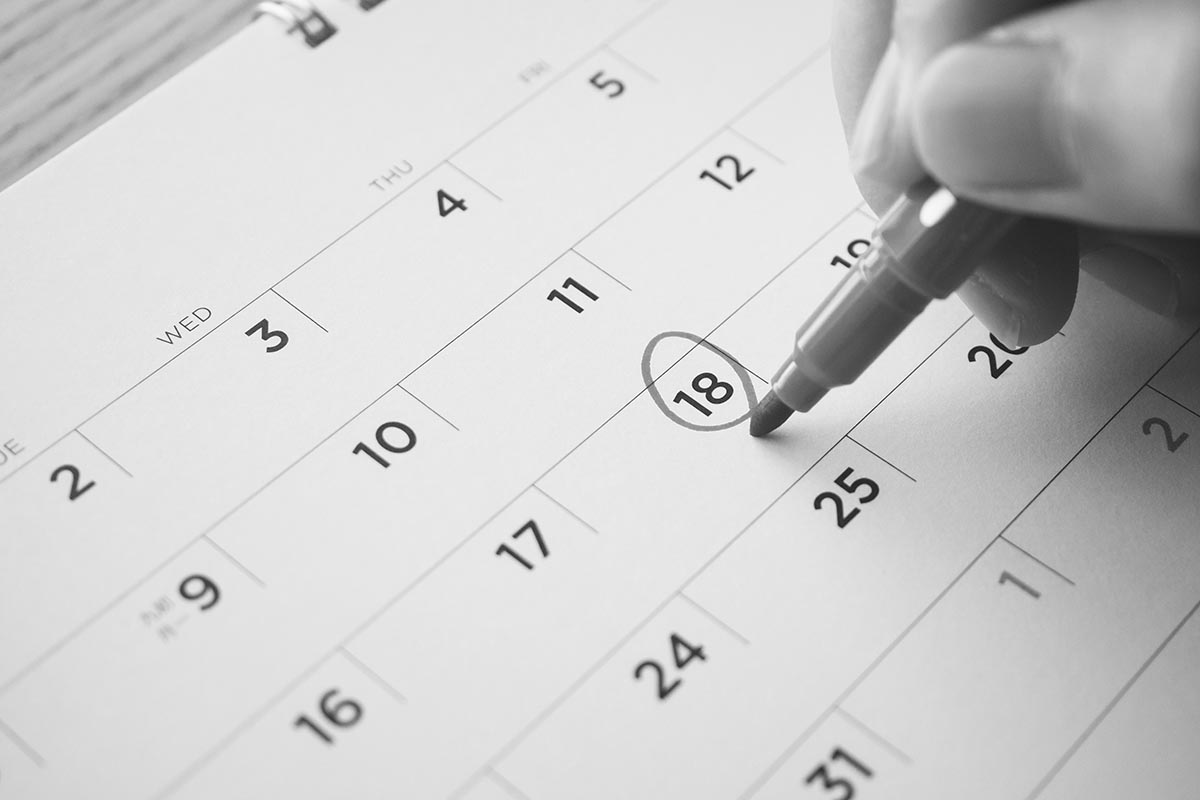 Female Hand with pen mark on calendar date